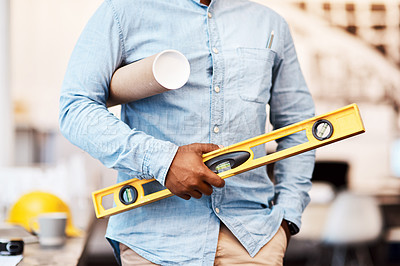 Buy stock photo Shot of an unrecognisable man holding a blueprint and spirit level in a modern office