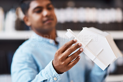 Buy stock photo Shot of a young architect designing a building model in a modern office