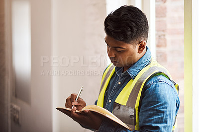 Buy stock photo Shot of a engineer making notes while on a construction site