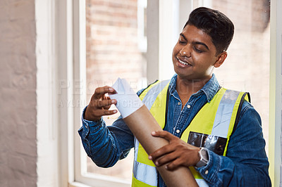Buy stock photo Shot of a young engineer holding a blueprint
