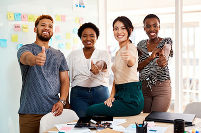 Buy stock photo Portrait of a group of young creatives showing thumbs up together in an office