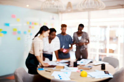 Buy stock photo Defocused shot of a group of young creatives working together in an office