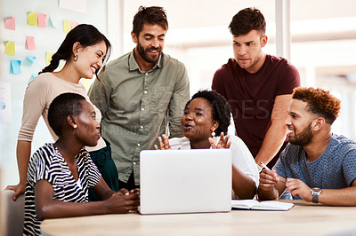 Buy stock photo Shot of a group of young creatives working together on a laptop in an office