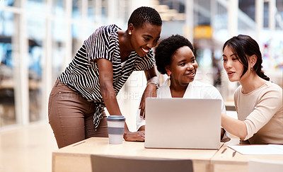 Buy stock photo Shot of a group of businesswomen working on a laptop together in an office