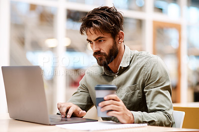 Buy stock photo Shot of a young businessman working a laptop while drinking coffee in an office