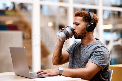 Buy stock photo Shot of a young businessman wearing headphones and drinking coffee while working on a laptop in an office