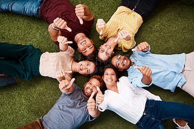 Buy stock photo Portrait of a group of young creatives showing thumbs up while lying down in a huddle together
