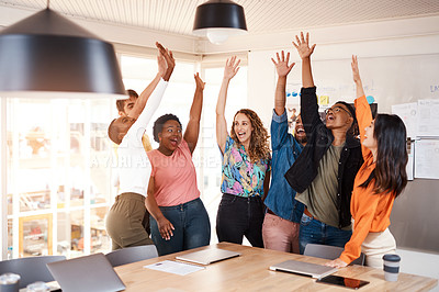 Buy stock photo Cropped shot of a group of young designers raising their hands in celebration while standing in the boardroom of their office