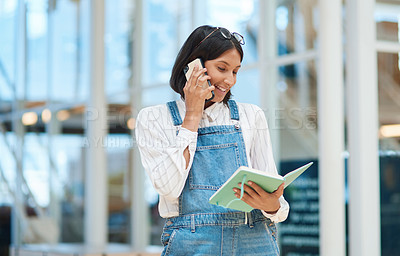 Buy stock photo Shot of a young businesswoman talking on a cellphone while going through a notebook in an office