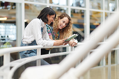 Buy stock photo Shot of two businesswomen going through a notebook together in an office