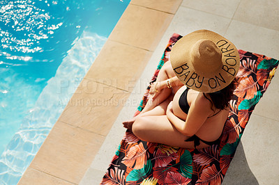 Buy stock photo Shot of a woman sitting by the pool while wearing a hat with