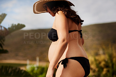 Buy stock photo Shot of a pregnant woman standing outside in her bikini