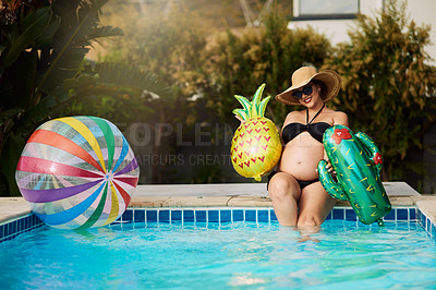 Buy stock photo Shot of a pregnant woman holding up inflatable foil balloons while spending time by the pool