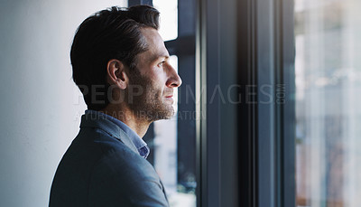 Buy stock photo Shot of a mature businessman looking thoughtfully out a window in an office