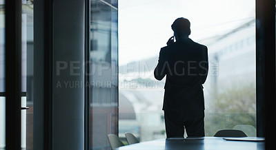 Buy stock photo Rearview shot of a mature businessman talking on a cellphone in an office