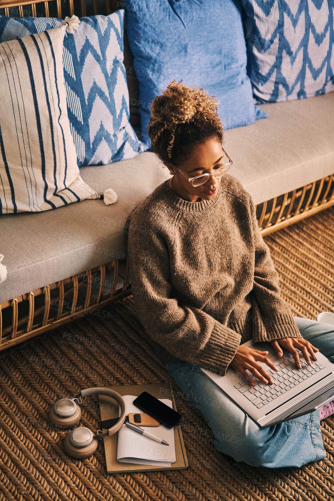 Buy stock photo High angle shot of a young woman using a laptop at home
