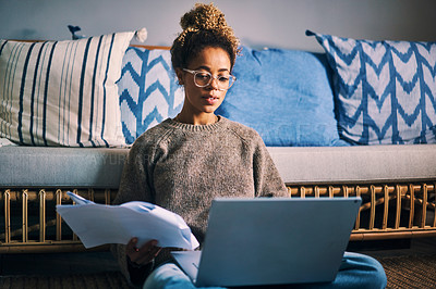 Buy stock photo Shot of a young woman going through paperwork while using a laptop at home