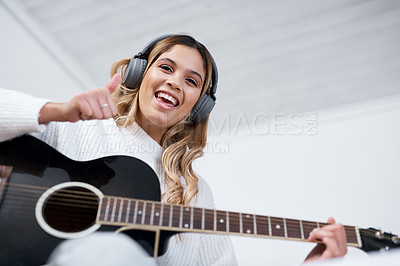 Buy stock photo Shot of a young woman wearing headphones while playing the guitar at home
