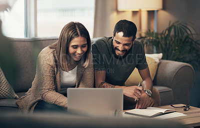 Buy stock photo Shot of a young couple using a laptop while going through paperwork at home