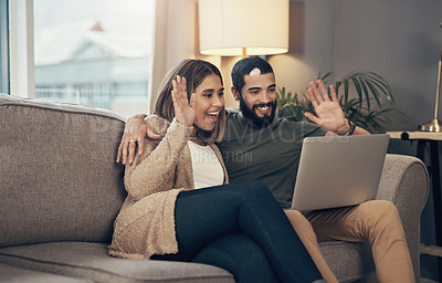 Buy stock photo Shot of a young couple using a laptop to make a video call on the sofa at home