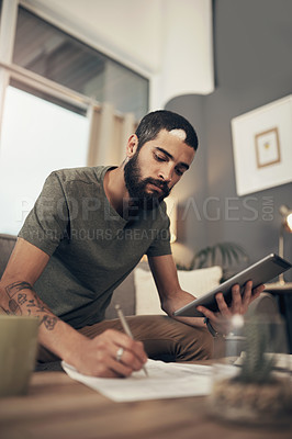 Buy stock photo Shot of a young man using a digital tablet while going through paperwork at home