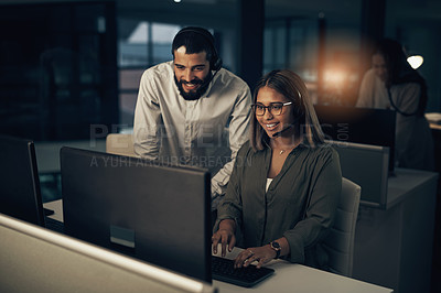 Buy stock photo Shot of two call centre agents working together in an office at night