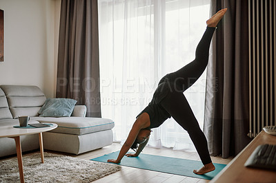 Buy stock photo Shot of a young woman practising yoga in her living room