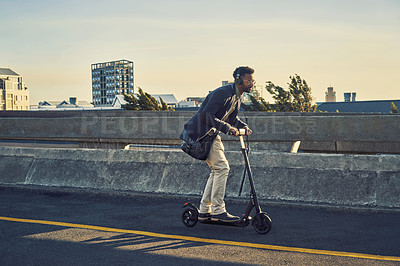 Buy stock photo Full length shot of a handsome young businessman travelling to work on his electric scooter