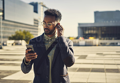 Buy stock photo Cropped shot of a handsome young businessman using his cellphone while out in the city