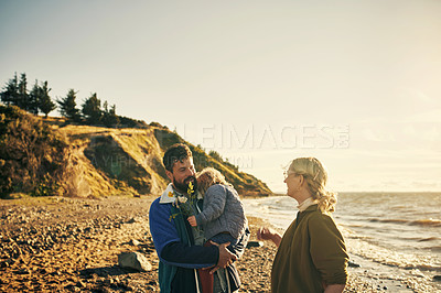 Buy stock photo Shot of a young couple and their daughter out on the beach together