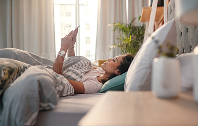 Buy stock photo Shot of a young woman using a cellphone while lying in bed at home