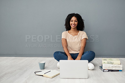 Buy stock photo Studio shot of a young woman using a laptop while completing her studies against a gray background