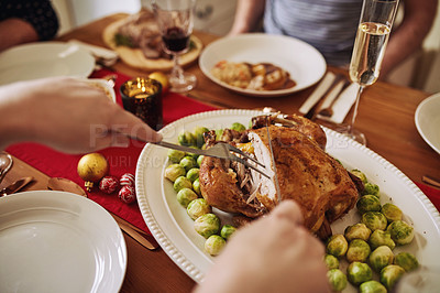Buy stock photo Cropped shot of an unrecognizable woman carving roasted chicken at Christmas lunch