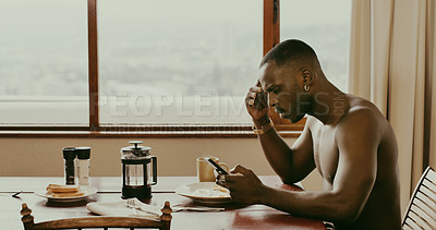 Buy stock photo Shot of a young man using his cellphone while having breakfast at home