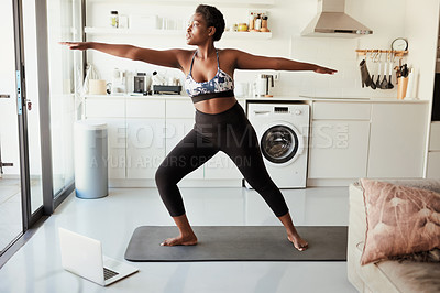 Buy stock photo Shot of a young woman using a laptop while exercising at home