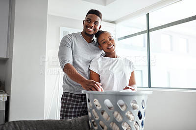 Buy stock photo Shot of a happy young couple doing laundry together at home