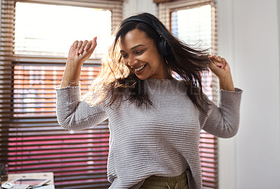 Buy stock photo Shot of a young woman dancing while listening to music at home