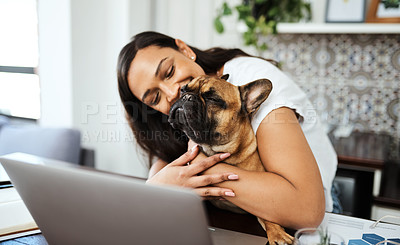 Buy stock photo Shot of a young woman sitting with her pet dog on her lap while working from home