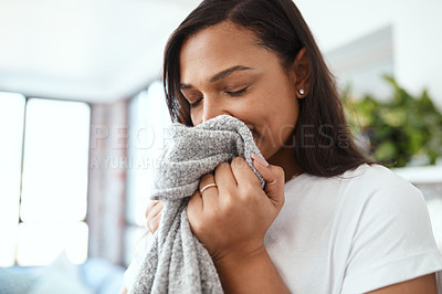 Buy stock photo Shot of a young woman smelling clean laundry at home