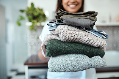 Buy stock photo Closeup shot of a young woman holding a pile of folded laundry at home