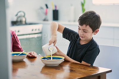 Buy stock photo Shot of a cute young boy and girl having cereal for breakfast at home