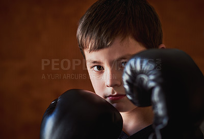 Buy stock photo Portrait of a young boy practicing a boxing routine against a brown background at home