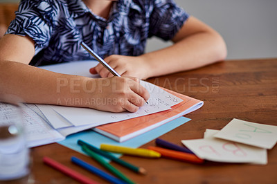 Buy stock photo Cropped shot of a little boy doing a school assignment at home