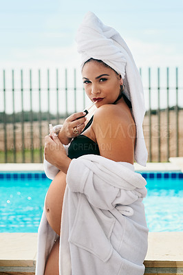 Buy stock photo Shot of a beautiful pregnant young woman putting on lipgloss while spending a relaxing day by the pool