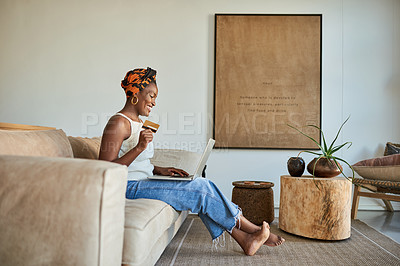 Buy stock photo Shot of a young woman using a credit card and laptop on the sofa at home