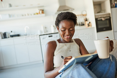Buy stock photo Shot of a young woman having tea and writing in a notebook on the sofa at home