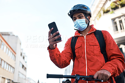 Buy stock photo Shot of a masked man using his cellphone while out on his bicycle for a delivery