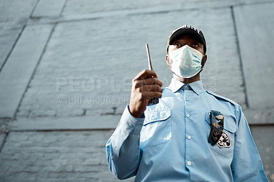 Buy stock photo Shot of a masked young security guard using a two way radio while on patrol outdoors