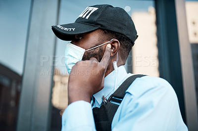 Buy stock photo Shot of a masked young security guard using an earpiece while on patrol outdoors