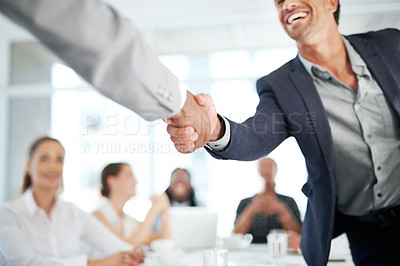 Buy stock photo Shot of two businesspeople shaking hands during a meeting in a boardroom